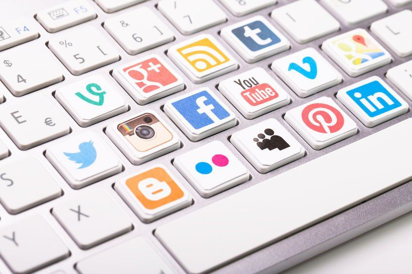 social media icons on a laptop keyboard: Twitter, Facebook, Instagram, YouTube, Pinterest, Tumblr, and more