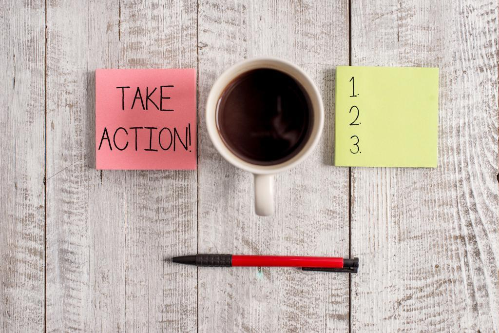 "post-it notes showing ""take action"" and steps 1, 2, and 3; a cup of coffee and a pencil on the table"