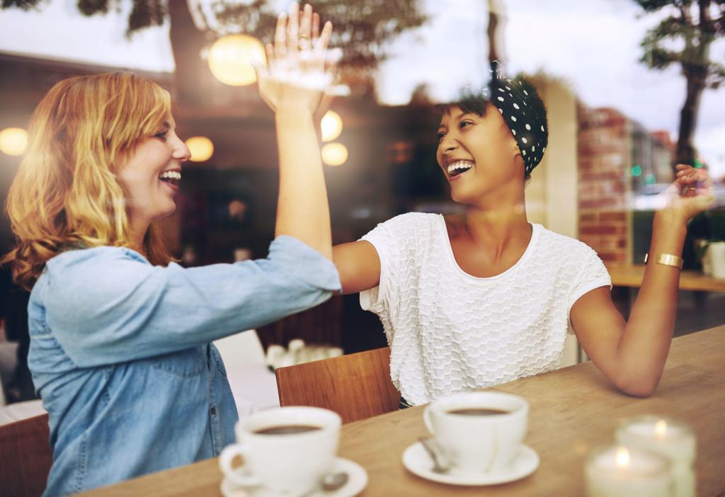 happy female friends high-fiving at a coffee shop