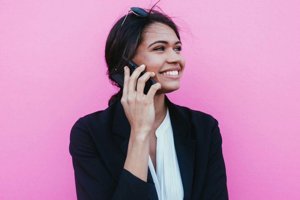 businesswoman smiling while on the phone, standing in front of a pink background