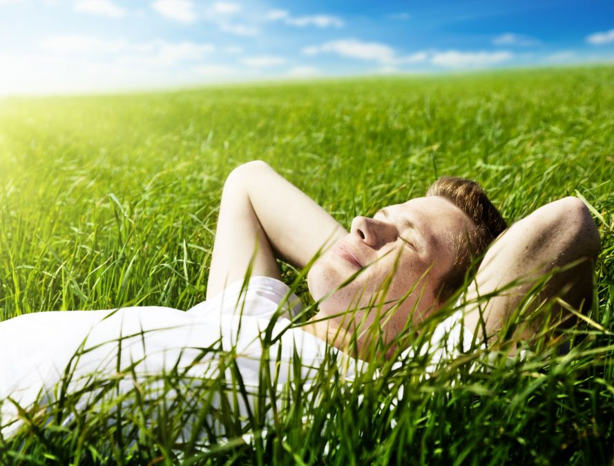 young man closing his eyes and lying in a field of green grass