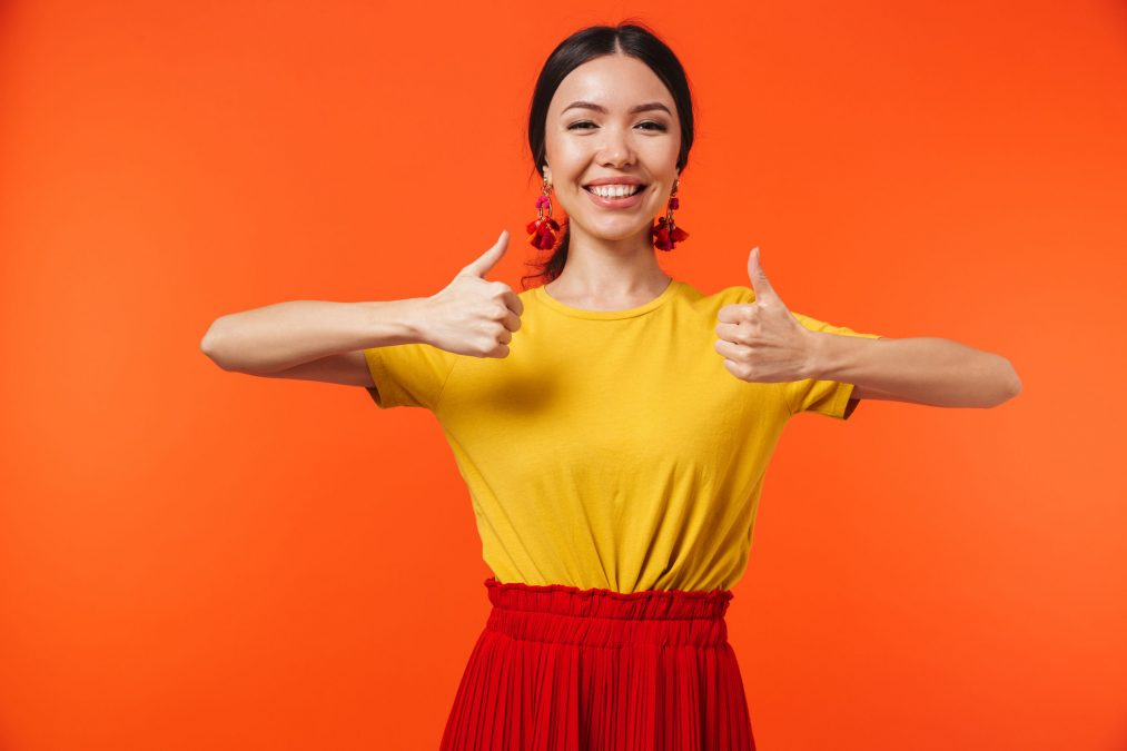 a happy young woman with two thumbs up on against an orange wall background