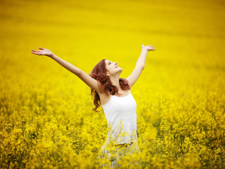 happy woman in a field of yellow flowers