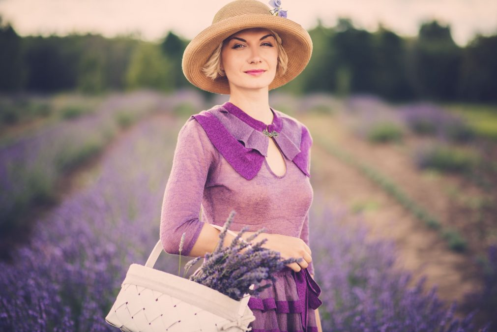 classy woman in a purple dress, standing in a field of lavender, with a basket of flowers