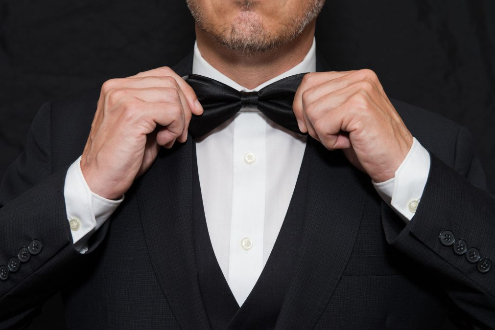 a man in a black tuxedo straightening his black bowtie