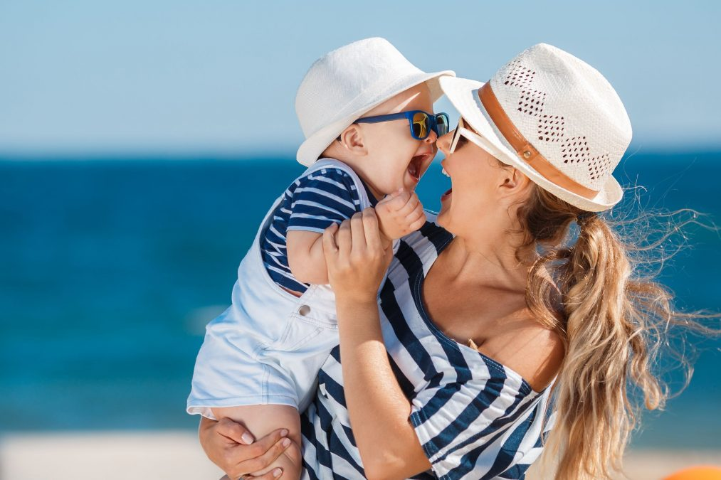 happy seaside mom and baby in matching blue-and-white striped shirts and white hats