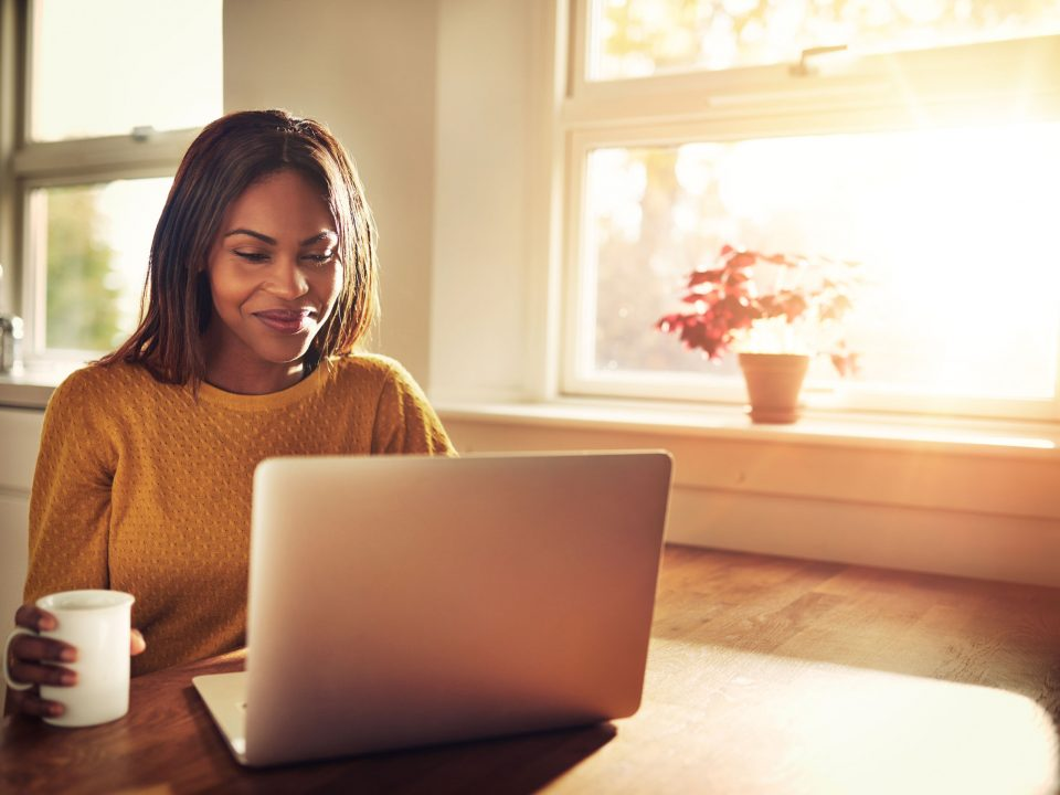 Woman smiling while drinking coffee and sitting with her laptop in the kitchen