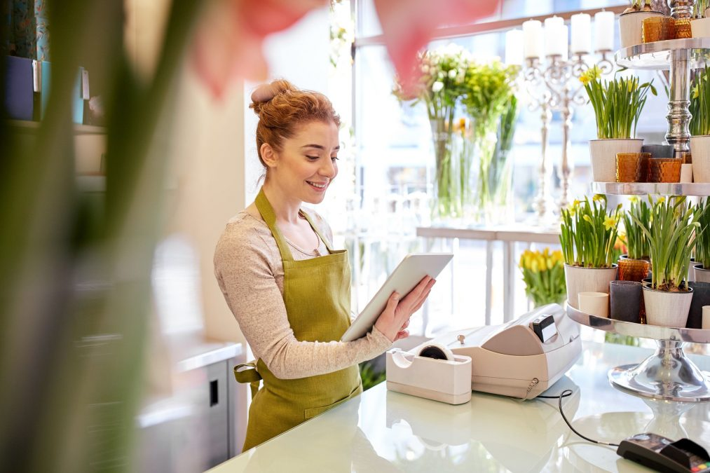 Small business owner checking her tablet, surrounded by flowers in a bright shop