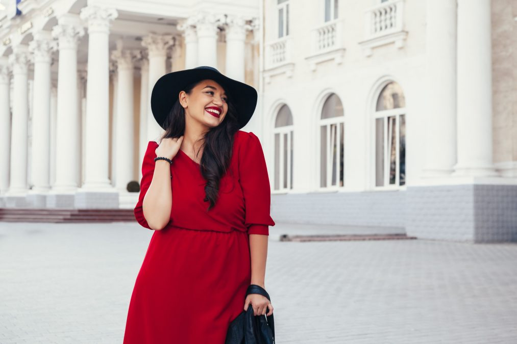 smiling brunette woman with red dress and lipstick outside a mansion