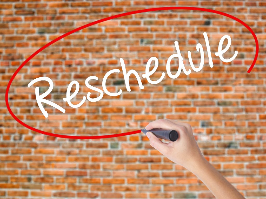 "a woman circling the word ""reschedule"" on a red brick wall background"