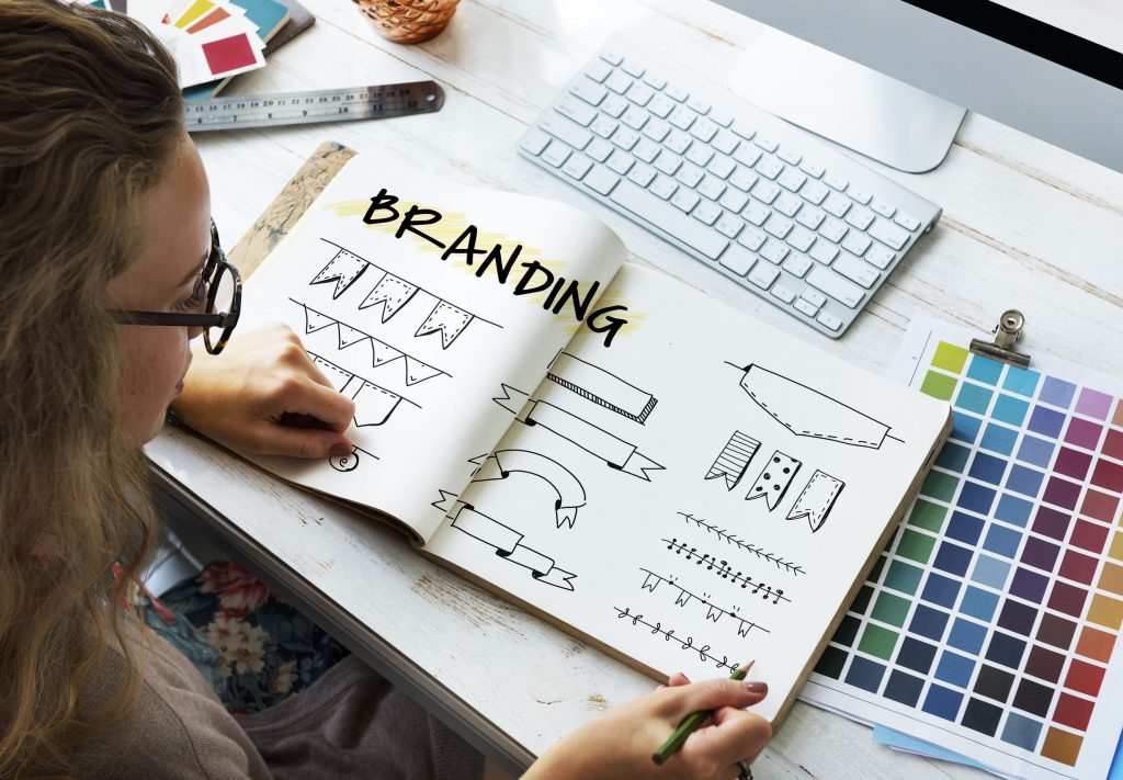 a designer looking at her branding book and various color palettes