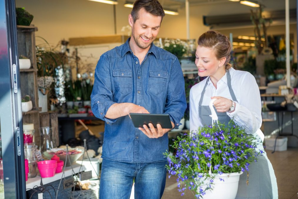 a male customer using a tablet to order from a female florist