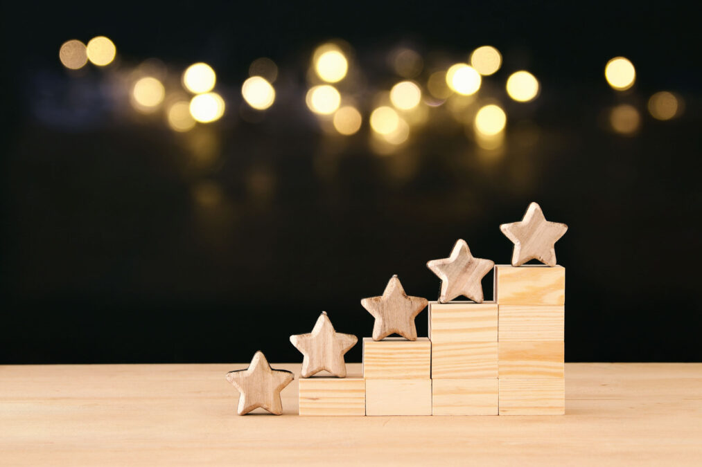 five stars on a mini wooden staircase with blurred lights on a dark background