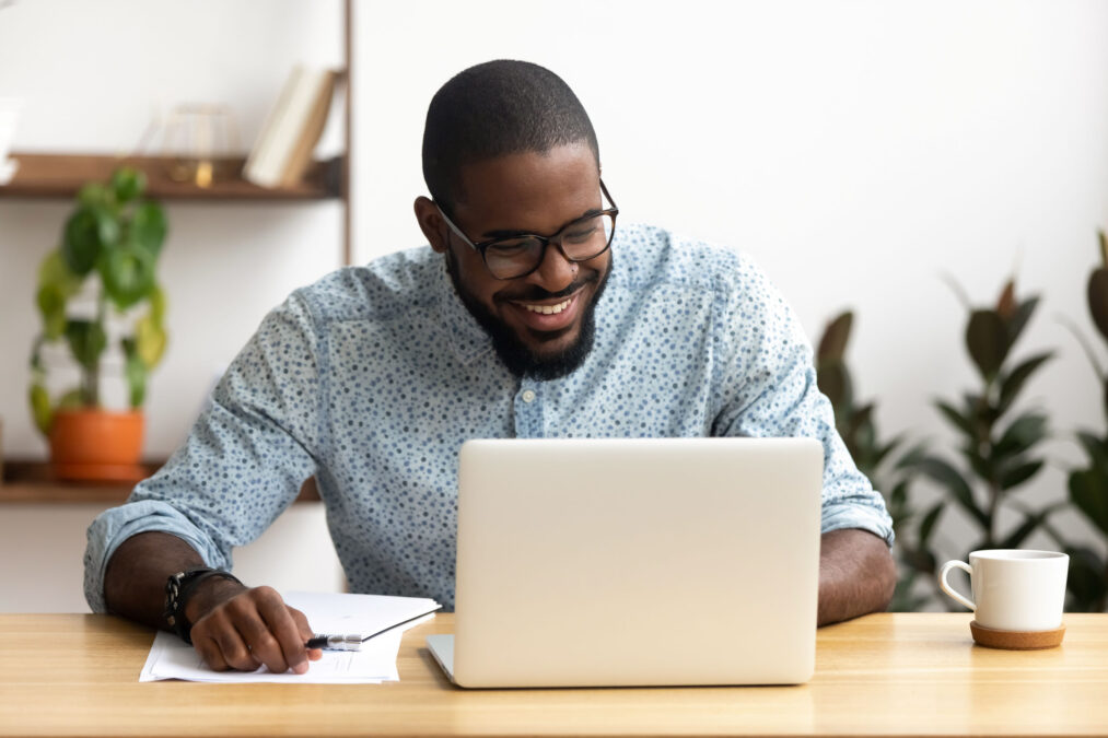 a smiling man on his laptop, planning social media for his small business