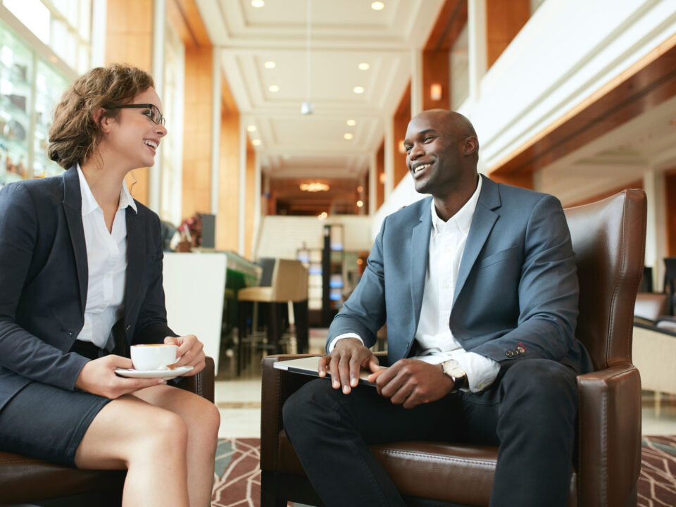 a marketer and her client, a business owner, laughing during a business meeting