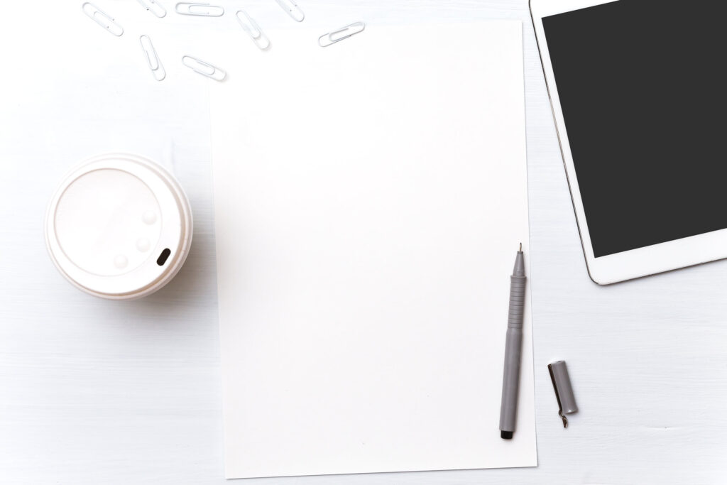 A designer going to start drawing on a blank white-colored piece of paper surrounded simply by paper clips, a pencil, coffee, and a tablet